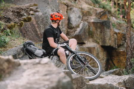 young trial biker relaxing on rocks with bicycle outdoors and looking at away 版權商用圖片