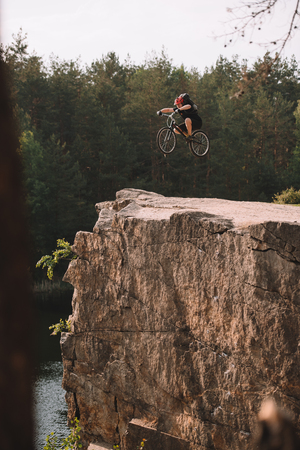 trial biker jumping on bicycle over rocky cliff outdoors in forest Stock Photo