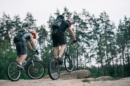 two male extreme cyclists in protective helmets riding on mountain bicycles in forest