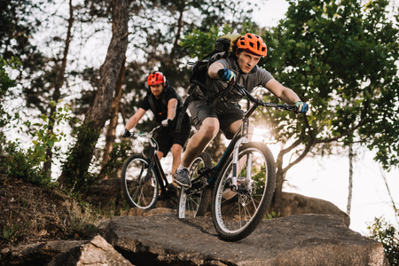 athletic young trial bikers riding on rocks at pine forest Stock Photo