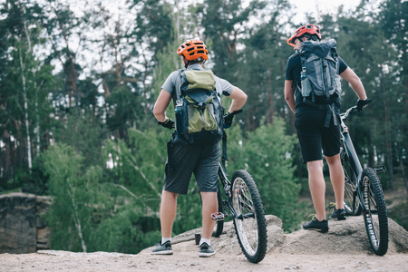 rear view of male extreme cyclists in protective helmets standing with mountain bicycles in forest