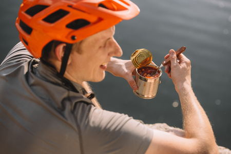 handsome young traveller in helmet eating canned food in front of water