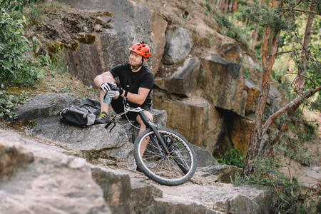 young trial biker relaxing on rocks with bicycle outdoors