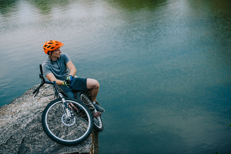 handsome young trial biker relaxing on rocky cliff over water Stock Photo