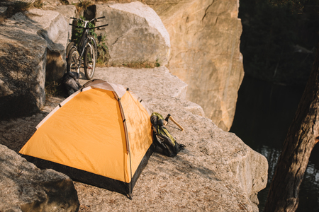 camping tent with trial bikes and backpack on beautiful rocky cliff Stock Photo
