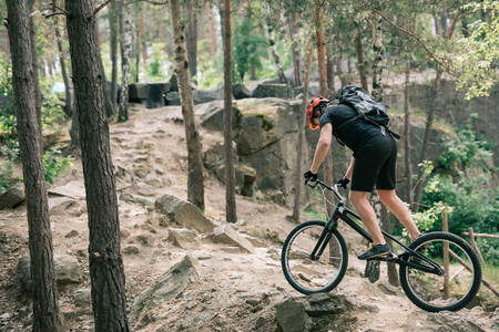 side view of male extreme cyclist in protective helmet riding on mountain bicycle in forest