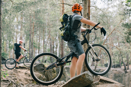 selective focus of male extreme cyclist on mountain bike talking to friend with bmx in forest Stok Fotoğraf