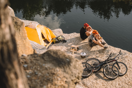 high angle view of active trial bikers eating canned food in camping on rocky cliff Banque d'images
