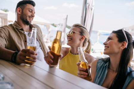 happy young man looking at beautiful smiling girls and drinking beer together at beach bar Reklamní fotografie