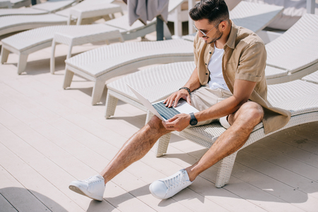 handsome young man sitting on chaise longue and using laptop at poolside