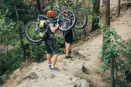 male extreme cyclists in helmets carrying mountain bikes in forest