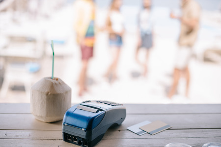 close-up view of summer cocktail with drinking straw and payment terminal with credit cards on bar counter at beach bar