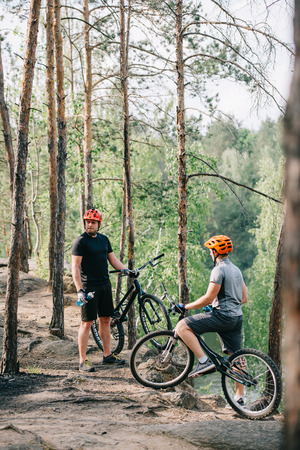 two male extreme cyclists in helmets with mountain bikes resting with sport bottles of water in forest
