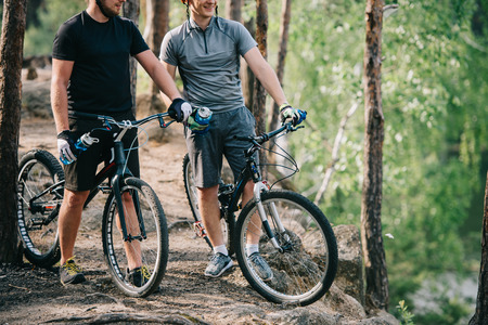 male extreme cyclists in helmets with mountain bikes resting with sport bottles of water in forest