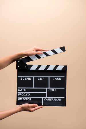 partial view of woman holding clapper board in hands isolated on beige