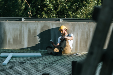 young builder in hardhat and protective googles using smartphone and resting at construction site