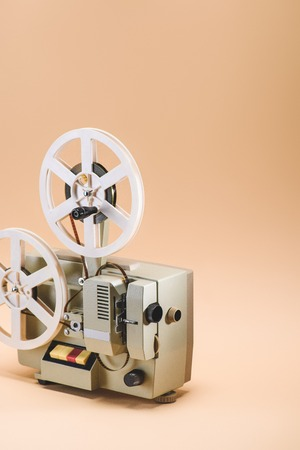 close up view of old film projector on beige background