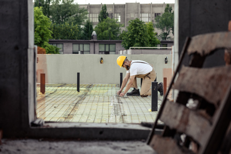 selective focus of builder in protective goggles and hardhat working at construction site