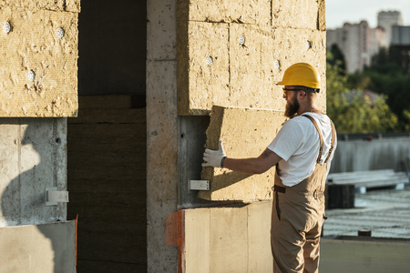 side view of builder in protective helmet and goggles doing insulation of wall at construction site Stockfoto