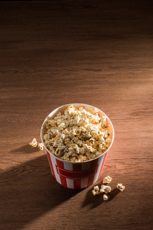 close up view of disposable bucket with popcorn on wooden tabletop Banco de Imagens