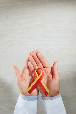 cropped image of female doctor holding ribbon, world hepatitis day concept Stock Photo