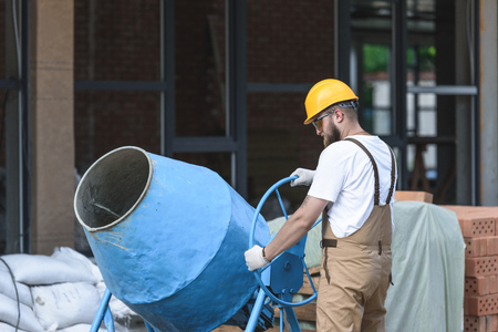 construction worker in hardhat and protective goggles working with concrete mixer on construction site Imagens