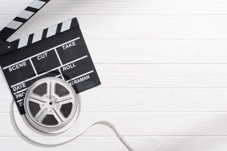 flat lay with clapper board and filmstrips on white wooden tabletop Stock Photo