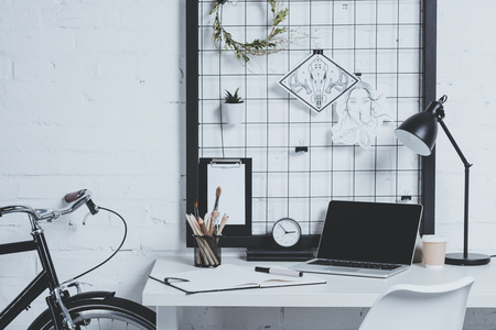 laptop on table in modern office, bicycle leaning on wall