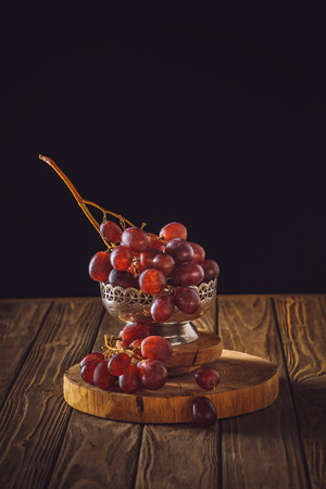 close-up shot of ripe grapes in vintage metal bowl on rustic wooden table on black