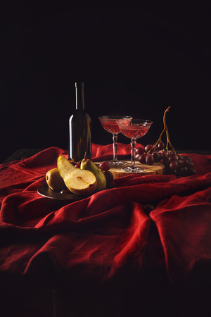 still life with pears, grapes and wine in bottle and crystal glasses on red drapery on black Stock Photo - 105956541