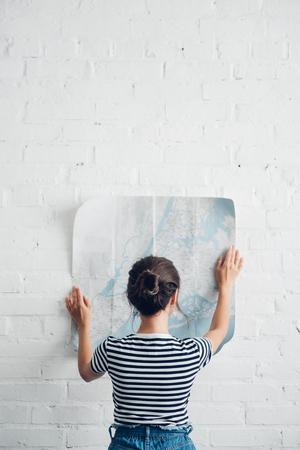 Vista trasera de una mujer mirando el mapa en las manos en la pared de ladrillo blanco, concepto de viaje