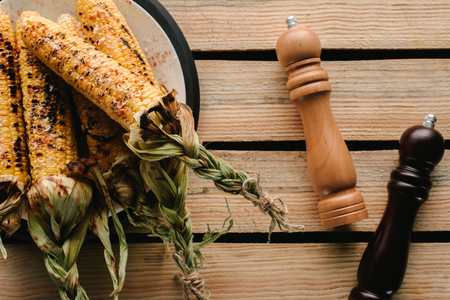 top view of grilled corn on plate near salt and pepper grinders on wooden table Banco de Imagens