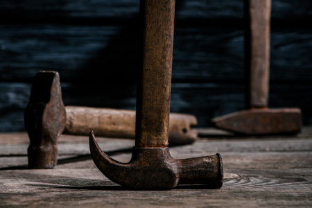 close up view of retro rusty hammers on wooden planks surface