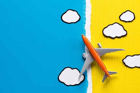 top view of toy plane and paper clouds on yellow and blue background, trip concept Banco de Imagens