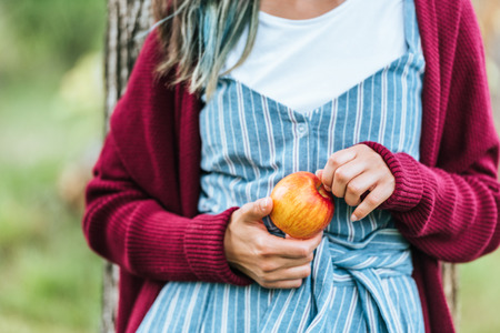 midsection view of girl holding fresh apple