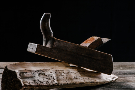 close up view of vintage woodworker plane and stump isolated on black