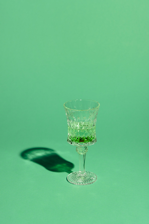 crystal glass of absinthe beverage on green surface