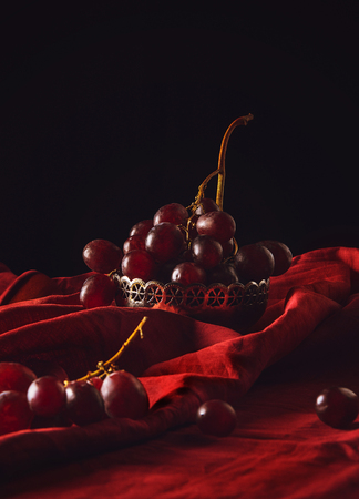 close-up shot of ripe grapes in vintage metal bowl on red drapery on black