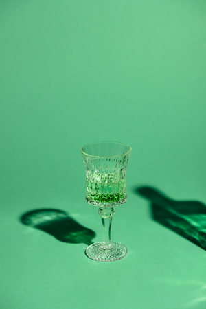 close-up shot of lead glass of absinthe on green surface Stock Photo