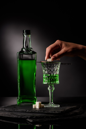 cropped shot of woman putting sugar cube on absinthe spoon on glass on dark background Stock Photo