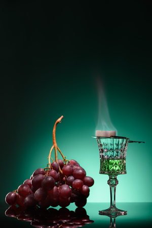 glass of burning absinthe with sugar and grapes on dark blue background Stock Photo