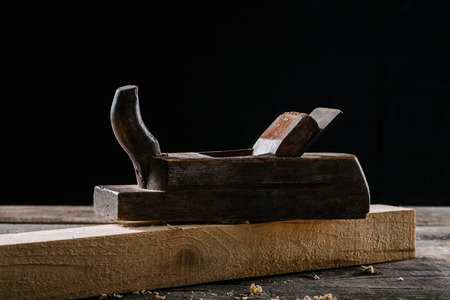 close up view of vintage woodworker plane and plank isolated on black 写真素材