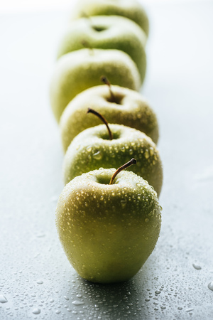 close up view of green apples with water drops on white background Stock Photo