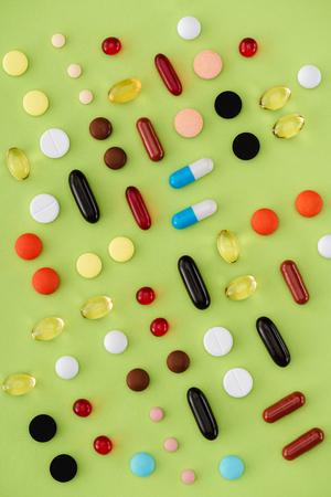 top view of arranged various pills on green background Zdjęcie Seryjne
