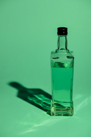 glass bottle of absinthe on green surface Stock Photo