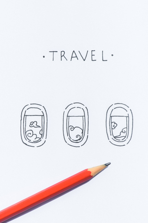 close up view of pencil on white paper with travel lettering and plane windows illustration