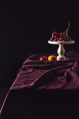 stand with grapes and apples on table with drapery on black