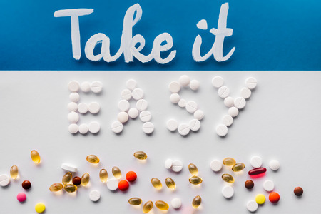 top view of lettering take it easy made by pills near various tablets on colorful background