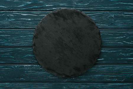 top view of round stone cutting board on green wooden tabletop