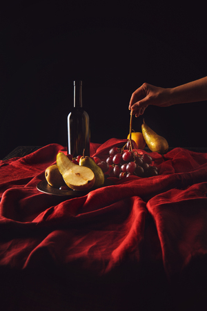 cropped shot of woman taking grapes from table with wine and pears on black Stock Photo